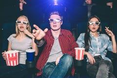 De verbaasde en verraste tieners letten op 3d film Zij dragen glazen voor dat De kerel probeert om het scherm met te bereiken Stock Foto's