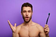 De verbaasde mens met wijd geopende mond, staart bij camera, houdt tandenborstel in hand stock foto's
