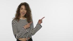 De verbaasde vrouw adverteert product met handgebaar Het verraste meisje toont exemplaarruimte stock videobeelden