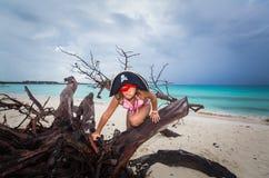 De verbazende grappige, ernstige zitting van de meisjepiraat op oude dode boom bij het strand tegen donkere dramatische hemel en  Royalty-vrije Stock Afbeeldingen