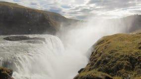 De verbazende grote waterval in zonnige dag in IJsland, plonsen vliegt omhoog, bewolkte hemel op achtergrond stock videobeelden