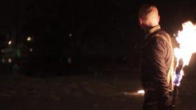 De verbazende stammenbrand toont dans bij nacht op de winter onder dalende sneeuw De dansgroep presteert met toortslichten en stock footage