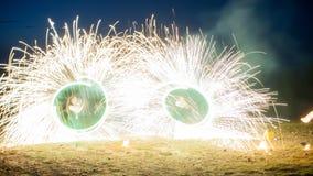 De verbazende twee uitvoerdersbrand toont met vuurwerk Dubbele o-Vorm volledig-om lijnen met heel wat vonken En rapt Stock Foto