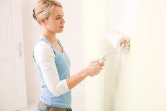 De verbetering van het huis - handywoman het schilderen muur stock foto
