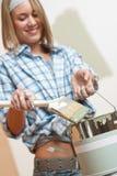De verbetering van het huis: Het glimlachen van de verf van de vrouwenholding kan Royalty-vrije Stock Foto