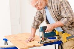 De verbetering van het huis - het hout van de manusje van allesbesnoeiing met figuurzaag stock foto's