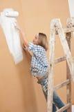 De verbetering van het huis: Het schilderen van de vrouw met verfrol stock foto
