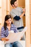 De verbetering van het huis jong paar met blauwdrukken stock fotografie