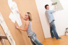 De verbetering van het huis: Jonge paar het schilderen muur Stock Fotografie