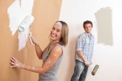 De verbetering van het huis: Jonge paar het schilderen muur stock afbeeldingen