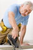 De verbetering van het huis, vernieuwing - mens die tegel legt stock foto