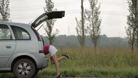 De verbijsterde Vrouw opent boomstam en neemt hulpmiddelen Vrouwelijke bestuurder, noodsituatie en drijfproblemen, gefrustreerd m stock videobeelden