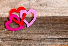 De verbonden harten van Valentine ` s op achtergrond van doorstaan hout Royalty-vrije Stock Foto's