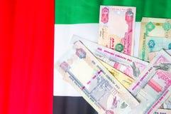 De verenigde Arabische munt van Emiraten bovenop vlag Stock Foto's