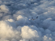 De verenigde vliegen van luchtvaartlijnenvliegtuigen in de donkere wolken met zonlicht Stock Fotografie