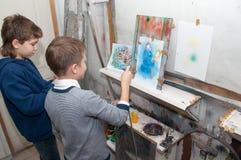 De verf van de jongenstiener met een luchtpenseel kleurde helder beelden in een artistical studio - Rusland, Moskou - Januari 24, Royalty-vrije Stock Fotografie