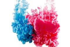 De verf van de kleureninkt in water, gefotografeerde die motie, op wit wordt geïsoleerd stock afbeelding
