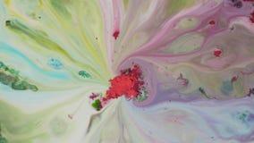 De verf van het kleurenpoeder wordt gemengd in water Het close-up van rood poeder in midden absorbeert kleurrijke wegspoelingen o stock footage