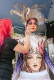 De Verf van kunstenaarsapplies colorful body aan Vrouwelijk Modelat festival Stock Afbeeldingen