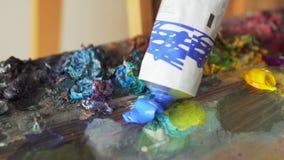 De verf van de kunstenaarssamendrukking uit buis in palet stock footage