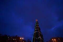 De verfraaide Kerstboom met een rode ster het gloeien steekt tegen de donkerblauwe hemel aan Royalty-vrije Stock Foto