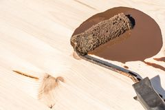 De verfrol met bruine houten vlek ligt op een houten raad stock fotografie