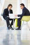 De Vergadering van zakenlieden met Laptop in Modern Bureau Royalty-vrije Stock Afbeeldingen