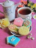 De verglaasde koekjes zijn op een lijst met een theepot en een kop thee, peperkoeken voor Moeder` s Dag Stock Foto