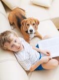 De verhalen van de jongenslezing voor zijn hond thuis Royalty-vrije Stock Foto's
