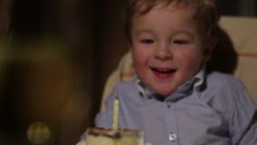 De verjaardag van het jonge geitje. De jongen blaast uit de kaars. stock video