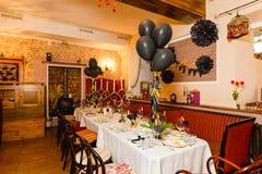 De verjaardagsgasten dienen het plaatsen met verse bloemen in zwarte en gouden stijl in, binnen Stock Foto