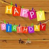 De verjaardagskaart met Wasknijper en de kleurrijke brieven hangen op kabel Royalty-vrije Stock Afbeeldingen