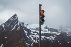 De verkeerslichten met rood zetten de achtergrond van snow-capped bergen aan stock afbeelding
