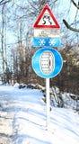 De verkeersteken met sneeuw ketenen aan boord van de auto Stock Foto