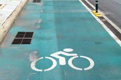 De verkeersteken van fietssteeg, sluiten omhoog wit fietser grafisch symbool op groene asfaltweg royalty-vrije stock afbeelding