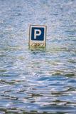 De verkeersteken van parkerenauto's die gedeeltelijk in een vloed worden ondergedompeld stock afbeelding