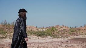 De verkenner in een zwarte mantel en een hoed is op de gebarsten grond in de woestijn stock video