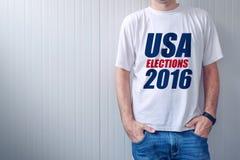 De verkiezingen 2016 die, mens van de V.S. t-shirt met gedrukt etiket dragen Royalty-vrije Stock Foto