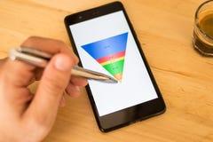 De verkoop concentreert getoond op een slimme telefoonvertoning, mannelijke hand die op gegevens richten Stock Foto