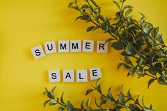 De verkoop van de inschrijvingszomer op de brieven van het toetsenbord op een gele achtergrond met takken bloeit stock foto's