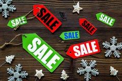De verkoop van Kerstmis De verkoop etiketteert dichtbij Kerstmisdecor op houten hoogste mening als achtergrond Stock Afbeelding