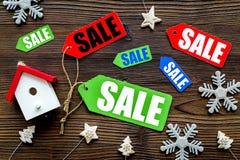 De verkoop van Kerstmis De verkoop etiketteert dichtbij Kerstmisspeelgoed op houten hoogste mening als achtergrond Royalty-vrije Stock Foto's