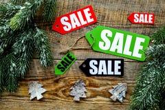 De verkoop van Kerstmis De verkoop etiketteert dichtbij net tak en Kerstmisdecor op houten hoogste mening als achtergrond Stock Foto