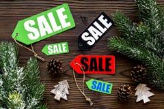 De verkoop van Kerstmis De verkoop etiketteert dichtbij net tak en Kerstmisdecor op houten hoogste mening als achtergrond Royalty-vrije Stock Foto's