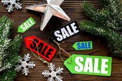 De verkoop van Kerstmis De verkoop etiketteert dichtbij net tak en Kerstmisdecor op houten hoogste mening als achtergrond Royalty-vrije Stock Afbeelding