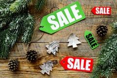 De verkoop van Kerstmis De verkoop etiketteert dichtbij net tak en Kerstmisdecor op houten hoogste mening als achtergrond Royalty-vrije Stock Afbeeldingen