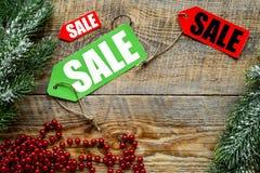 De verkoop van Kerstmis De verkoop etiketteert dichtbij net tak en Kerstmisdecor op houten hoogste mening als achtergrond copyspa Royalty-vrije Stock Fotografie