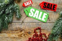 De verkoop van Kerstmis De verkoop etiketteert dichtbij net tak en Kerstmisdecor op houten hoogste mening als achtergrond copyspa Royalty-vrije Stock Afbeeldingen