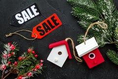 De verkoop van Kerstmis De verkoop etiketteert dichtbij net tak en Kerstmisspeelgoed op zwarte hoogste mening als achtergrond Stock Fotografie