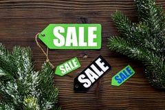 De verkoop van de winter De verkoop etiketteert dichtbij nette takken op houten hoogste mening als achtergrond Royalty-vrije Stock Fotografie